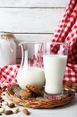 picture of caw  - Milk in glassware with walnuts and cookies on wooden table with napkin - JPG