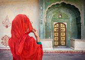 stock photo of rajasthani  - Woman in red scarf looking at green gate door in City Palace of Jaipur Rajasthan India - JPG