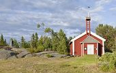stock photo of chapels  - Red wooden chapel in sunny evening lit by the sea - JPG