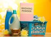 picture of detergent  - Clothes with detergent and washing powder in plastic basket on yellow background - JPG