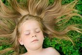 Little girl laying on the grass