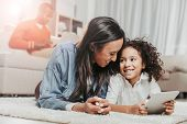 Satisfied Mother And Child Hanging Out Together. They Are Relaxing On Rug With Tablet And Looking At poster
