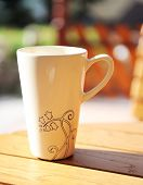 White mug on a table with outdoor setting