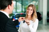 image of rep  - Woman at a car dealership buying an auto - JPG