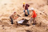 Diamond Mining And Treasure Search Concept. Figurines Digging Gemstone Out Of Sand poster
