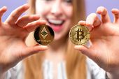 Woman Holding Physical Bitcoin And Ethereum Cryptocurrency Coins In Her Hands poster