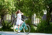 Long Haired Young Woman In A Dress Riding Bicycle In The Bark Copyspace Emotions Freedom Freshness W poster