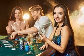Group Of An Elegant People Playing Poker At The Gambling House. Focus On A Emotional Brunette In A B poster