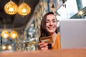 Payment Opportunities. Low Angle Of Positive Young Brunette Woman Carrying Credit Card While Smiling poster