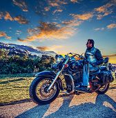 Biker On A Classic Motorcycle On The Edge Of The Road At Sunset poster