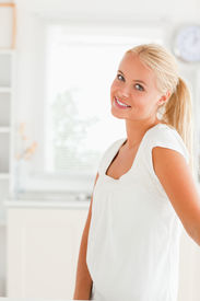 stock photo of blonde woman  - Woman standing in her kitchen while looking at the camera - JPG
