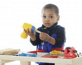 Closeup image of an adorable toddler playing carpenter with plastic tools on a work bench.  On a whi