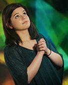 eine schöne junge Teenager nachschlagen, wie sie mit Hände gefaltet betet. vor dem Hintergrund Glasmalerei