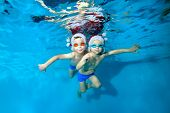 Two Little Boys Swim And Pose Underwater In Red Santa Hats And Swimming Goggles. They Hug, Look At T poster