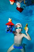A Little Boy Poses Underwater With Christmas Toys In His Hands, Wearing A Red Santa Hat And Swimming poster
