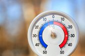 Outdoor thermometer with Celsius scale showing cold minus 5 degrees temperature - dramatic weather c poster