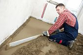 Plasterer at indoor concrete cement floor topping with screed sleeker