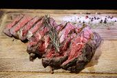 Medium-roasted Steak Cut Into Pieces On A Wooden Board With Sauce And Seasonings. Delicious Steak. B poster