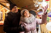 shopping, winter holidays and people concept - happy senior couple at christmas market souvenir shop poster