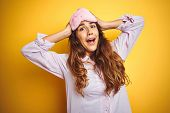 Young woman wearing pajama and sleep mask standing over yellow isolated background Crazy and scared  poster