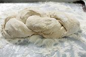 A piece of bread dough that has been plaited and is waiting to rise before being baked.