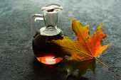 Bottle With Maple Syrup And Maple Leaf On A Black Background. poster