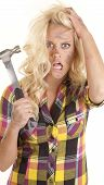foto of frazzled  - A woman is holding a hammer in her hand and looks very frustrated - JPG