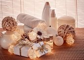 Spa still life with cosmetic creams,  towel, gift boxes and Christmas ornaments standing on bamboo m poster