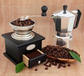 Coffee grinder, espresso percolator, beans and leaf sprigs over papyrus background.