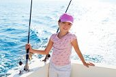child girl sailing in fishing boat holding rod in blue sea