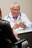 picture of ob-gyn  - Senior male doctor going through a medicine box while female sitting on chair - JPG