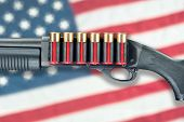 picture of ammo  - A shotgun with red shell cartridge ammo isolated against an American flag - JPG