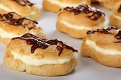 foto of eclairs  - Cream filled eclair with chocolate icing on baking sheet - JPG