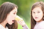 Daughter poked mother with ice cream in her face.