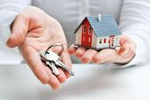 foto of possess  - Real estate agent with house model and keys - JPG