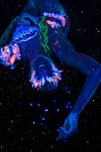 Beautiful lying woman with body art glowing in ultraviolet light