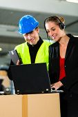 Teamwork - warehouseman or forklift driver and female supervisor with laptop, headset and cell phone