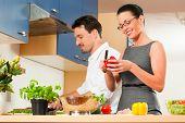Mann und Frau in der Küche - sie Vorbereitung der Gemüse und Salat für Mittag- oder Abendessen