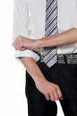 ein junger erfolgreicher Mann rollt seine Ärmel