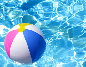 stock photo of beach-ball  - Multi colored Beach ball in swimming pool - JPG