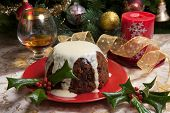 pic of vanilla  - Christmas pudding with white vanilla sauce on holiday table decorated with holly twig glass of brandy ornaments candles and xmas tree - JPG