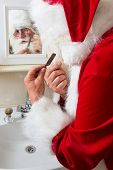 Funny Santa Claus shaving off his mustache and beard