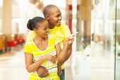 happy young african couple shopping in mall