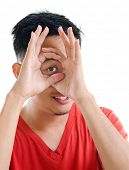 foto of peep hole  - Asian man peeping through fingers hole - JPG
