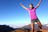 Success winner fitness runner woman jumping happy, excited and energetic with happy cheering face expression celebrating. Sporty running girl cheering after training outdoor in volcano landscape.