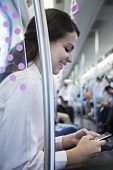 Young businesswoman sitting on the subway and using her phone