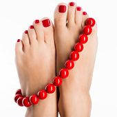 image of pedicure  - Closeup photo of a female feet with beautiful red pedicure and big beads  - JPG