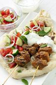 Tandoori lamb kebabs with naan bread, salad, and minted yogurt.