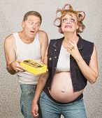 stock photo of redneck  - Moody redneck hillbilly pregnant couple with candy - JPG