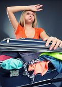 Exhausted young woman packing luggage for vacations